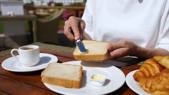 Woman Having Breakfast With Coffee, Toasts, Butter And Jam Outdoors