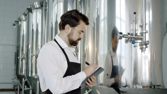 Brewery Worker Checking Beverage Equipment at Brewery or Beer Plant. Beer Production.