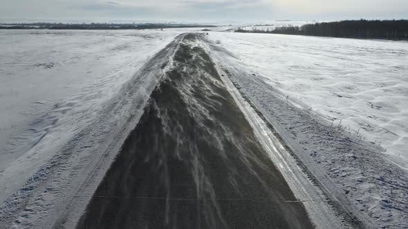 Cover Image for Flight at Low Altitude Over the Winter Road Wind Overtakes the Snow Across the Road