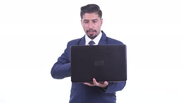 Thumbnail for Happy Bearded Persian Businessman Talking While Using Laptop