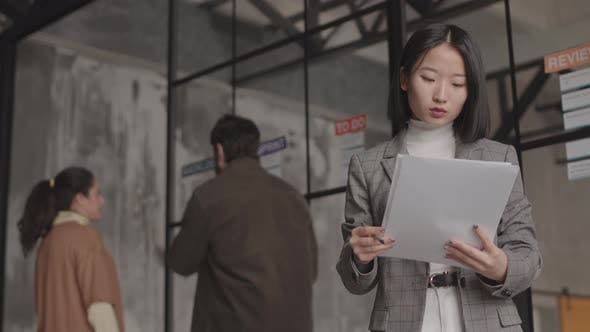 Asian Businesswoman Posing with Papers