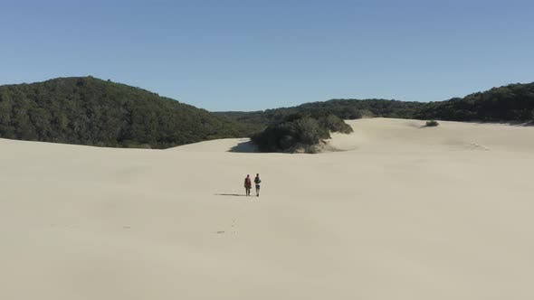 Aerial view of couple walking in sand dunes