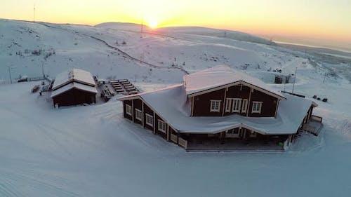 Fliegen über das Winterskizentrum bei Sonnenuntergang