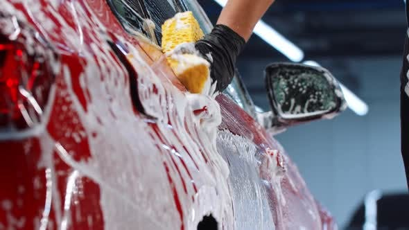Auto Cleaning Service  Man Worker Cleaning the Car Surface with a Yellow Sponge