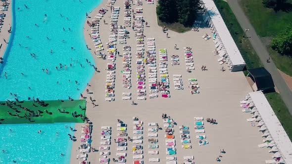 Thumbnail for Aerial: Flying Over the Beach, a Lot of People Are Sunbathing, Swimming in the Pool