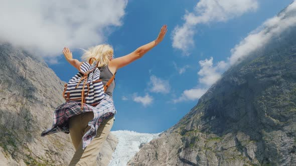 Thumbnail for A Young Active Woman Raises Her Hands Up, Standing Against the Background of a Mountain with a