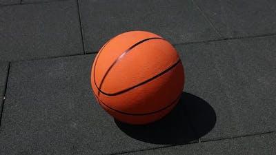 Basketball ball spinning on street paving