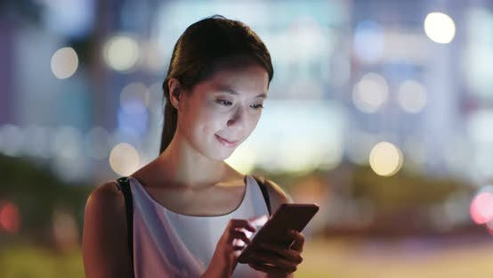 Thumbnail for Woman sending sms on cellphone at night