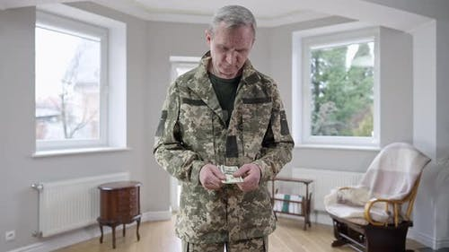 Middle Shot Portrait of Sad Middle Aged Soldier Holding Money and Thinking