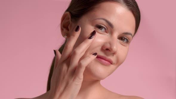 30er Jahre Brünette Frau mit idealer Haut im Studio auf rosa Hintergrund