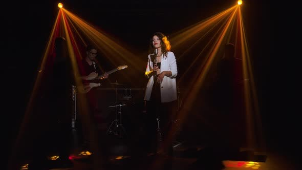 Cover Image for A Stylish Girl Vocalist Sings on Stage in a Vintage Microphone. In the Background Musicians