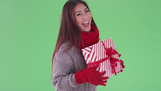 Thumbnail for Happy asian woman holding presents in the snow on green screen