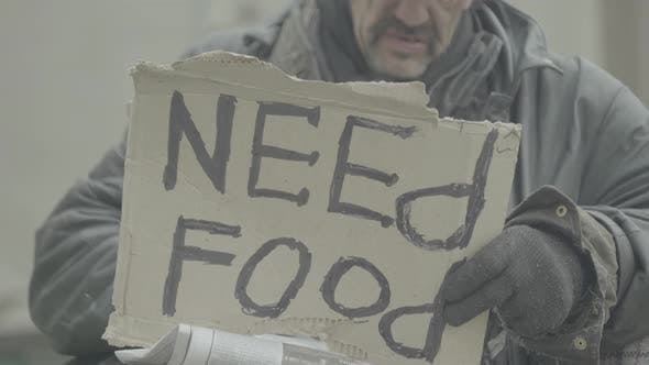 """Thumbnail for Die Inschrift """"Brauchen Nahrung"""" von einem armen Obdachlosen Landstreicher. Kiew.  Ukraine"""