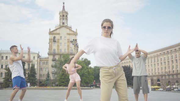 Thumbnail for Camera Approaches To Cheerful Young Girl Dancing Robot Dance on Sunny City Square with Group of
