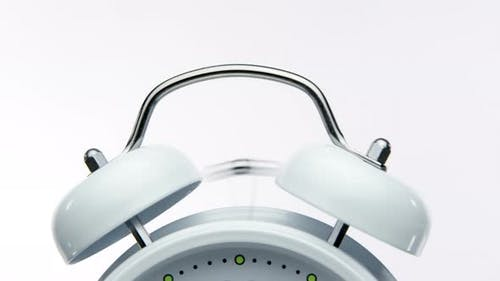 Close Up Bell of Vintage White Alarm Clock Triggers Alarm on White Background