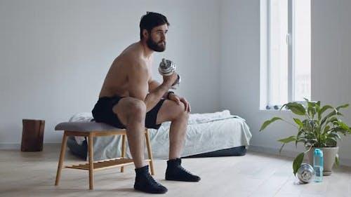 Junger Mann mit nackten Torso Lifting Hantel zu Hause