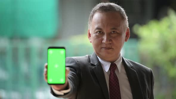 Thumbnail for Mature Japanese Businessman Showing Phone in the Streets Outdoors