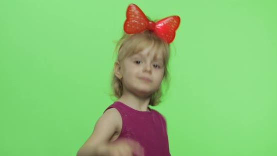 Girl in Purple Dress Dancing and Shows a Finger Forward. Happy Child. Chroma Key