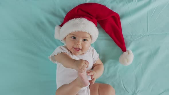 Funny Little Baby Smiling of the 2021 Year. Cute Infant Boy Wearing Santa Hat Lying on Sofa.