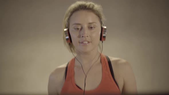 Thumbnail for Portrait of Charming Young Woman in Headphones Walking on Treadmill. Close-up Face of Beautiful
