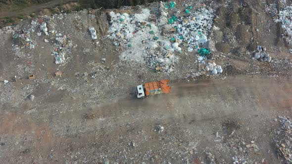 Thumbnail for Aerial Shot of Big Rubbish Pile Lying Among Field in Countryside. Flying Over Garbage
