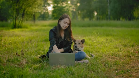 Thumbnail for A Woman in a Park Next To an Open Laptop Is Petting Her Dog.
