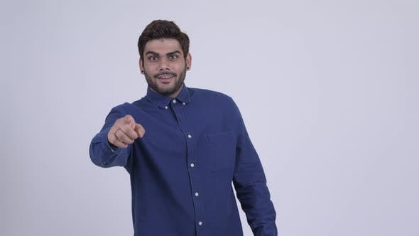 Thumbnail for Happy Young Bearded Indian Businessman Pointing at Camera