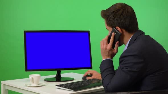 Thumbnail for A Young Businessman Works on a Desktop Computer and Talks on a Smartphone - Green Screen Studio
