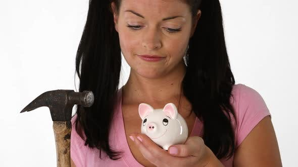 Thumbnail for Closeup portrait of young woman holding a piggy bank and hammer