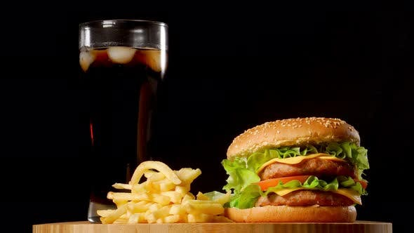Cover Image for Burger with French Fries and a Glass with Ice Cola on a Black Rustic Background
