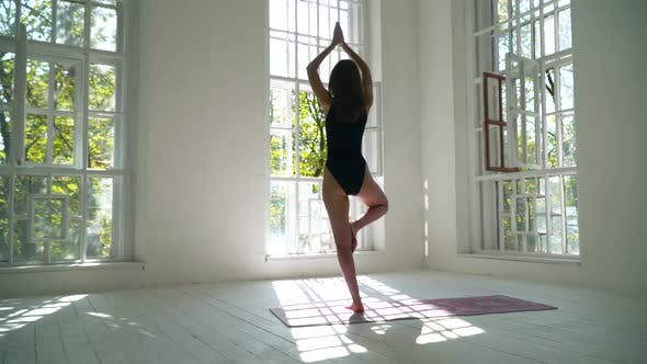 Thumbnail for Healthy Caucasian Woman Standing on the Mat in the White Large Room Practicing Yoga. Young Woman