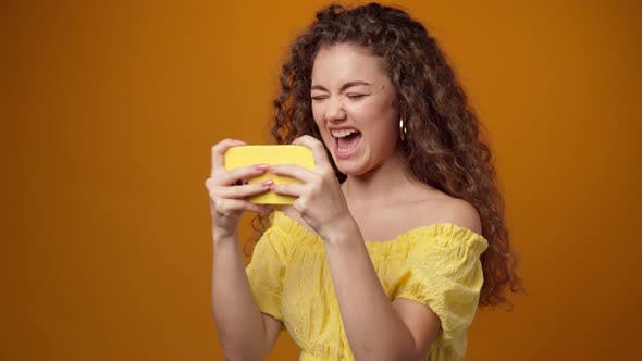 Young Curly Woman Playing Games on Smartphone Against Yellow Background