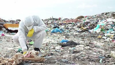 Virologist in Protective Costume and Gas Mask Coming and Examining Landfill
