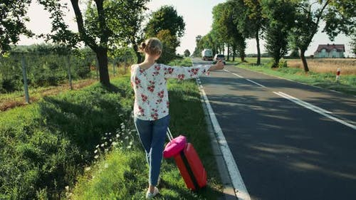 Anonymous Young Lady Hitchhiking on Countryside Road.