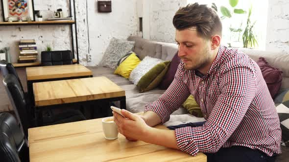 Thumbnail for The Customer Is Using His Phone While Drinking Coffee