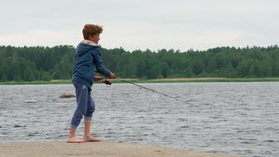 Boy With A Spinning Rod On A Lake Pier