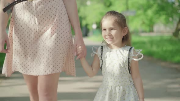 Thumbnail for Portrait of Charming Brunette Brown-eyed Girl Strolling with Mom in Sunny Park. Cute Little