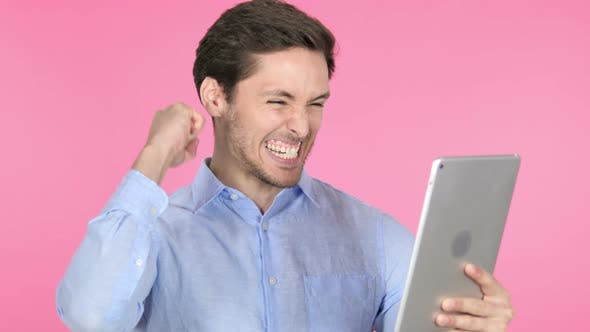 Thumbnail for Young Man Celebrating Success on Tablet, Pink Background