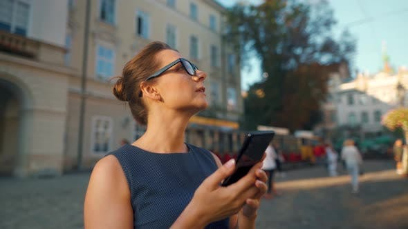 Woman in Glasses Standing on an Old Street, Using Smartphone and Looking Around