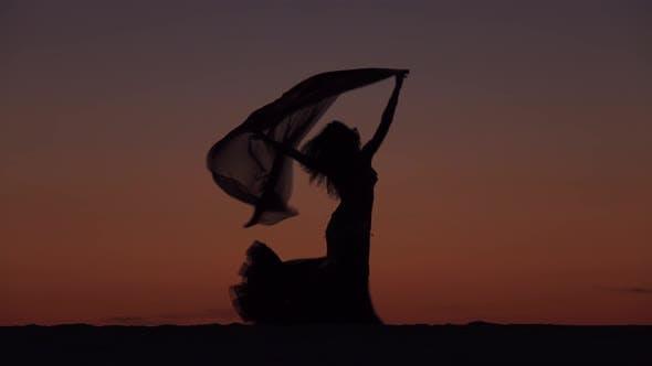 Thumbnail for Girl on the Seashore Gracefully Dances Her Body Against the Sunset, Silhouette