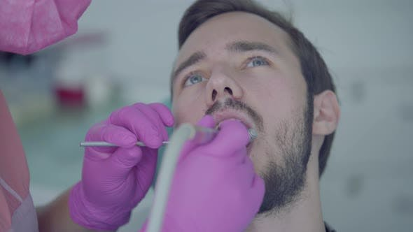 Thumbnail for Dentist in Medical Mask and Gloves Checking the Tooth of the Patient Using Medical Tools