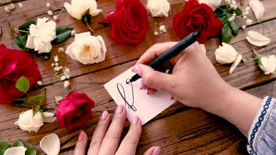 Writing FLOWERS on a card near flowers close up