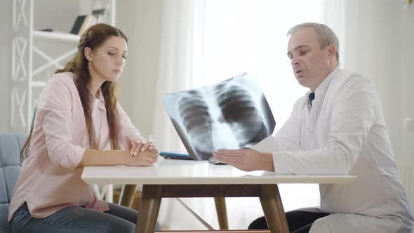 Thumbnail for Professional Physician Explaining Lungs X-ray To Young Woman in Hospital, Side View Portrait of Mid