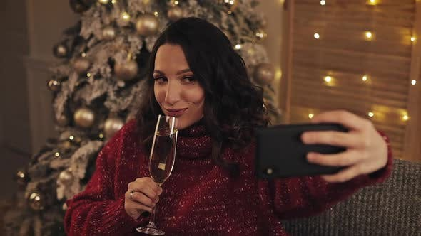 Thumbnail for Young Attractive Woman Making Selfie Photo with Sparkling Wine on Christmas Interior Background