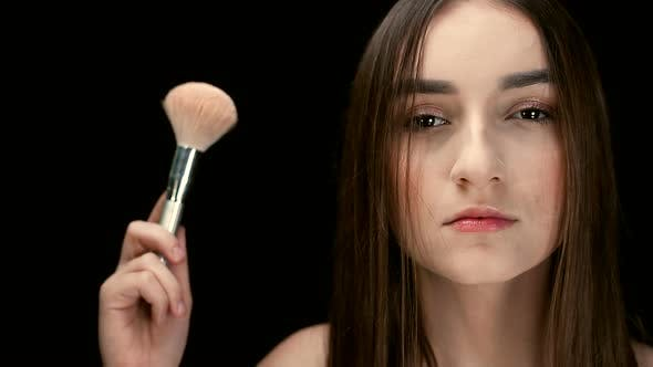 Fashion Model Girl Holds a Powder Brush in Her Hand and Shakes Off the Powder. Small Particles