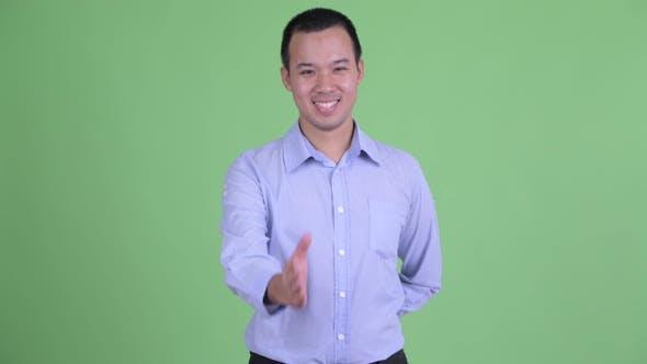 Thumbnail for Studio Shot of Happy Asian Businessman Giving Handshake
