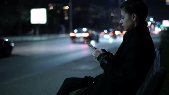 Thumbnail for Lonely Woman Using Mobile Phone at Night on Street with Night Traffic Passing By