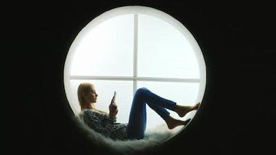 Student Lies Inside a Round Window Reads an Ebook