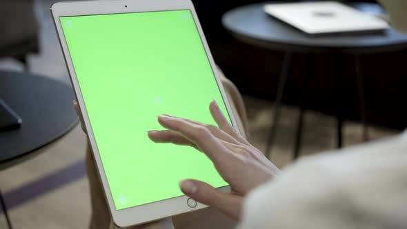 Thumbnail for Woman Swiping On Green Screen Display Of Tablet