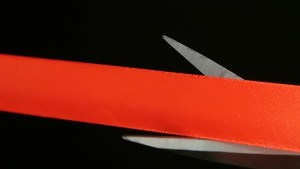 Thumbnail for On a Black Background Cut Red Ribbon Scissors. Slow Motion